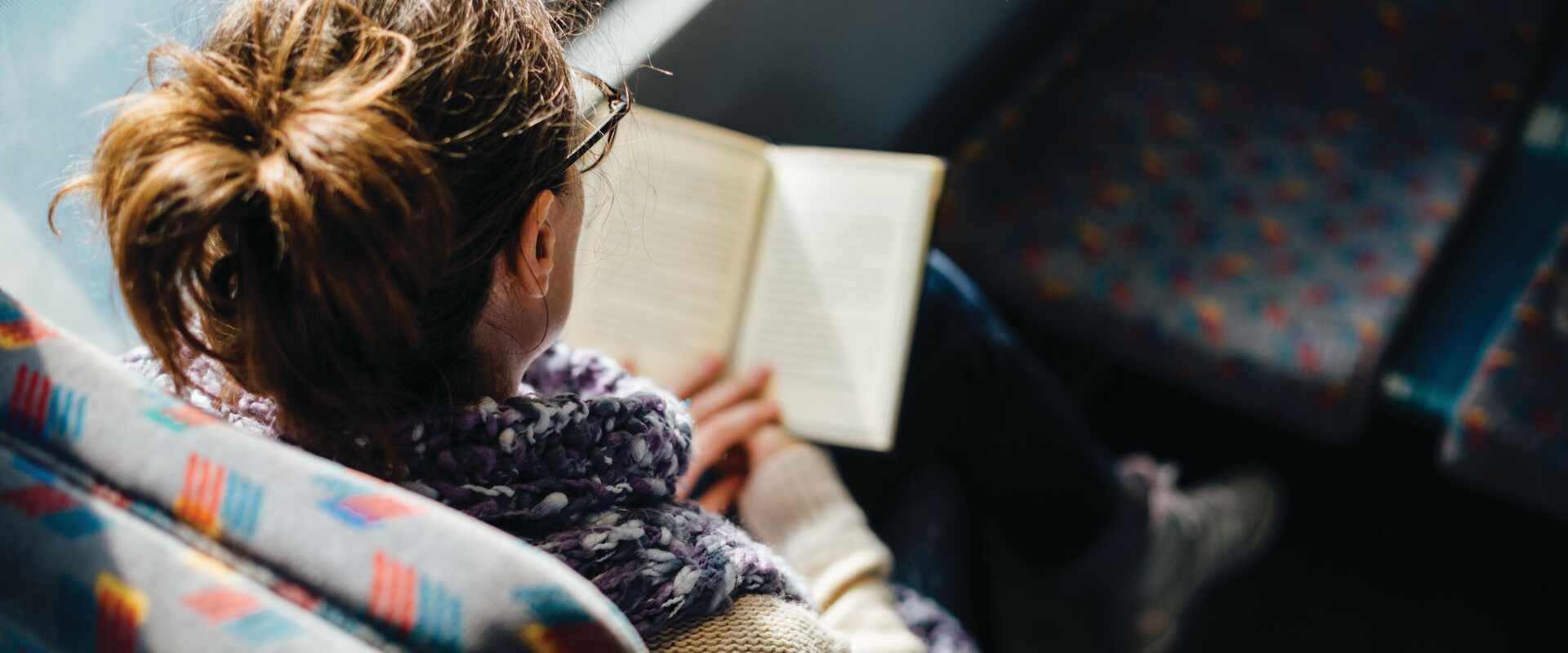 Person reading book on train