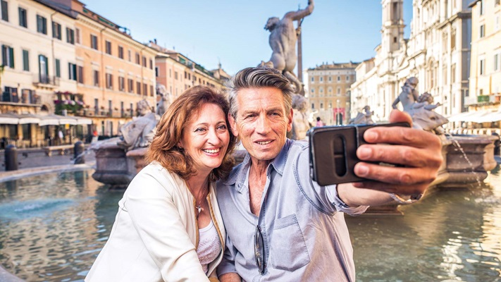 View of a couple sitting by a fountain taking a selfie, italy