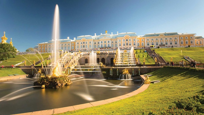 View of the exterior of a palace with a garden of waterfountains and lush green grass, Russia