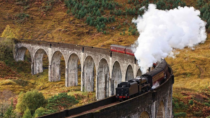 View of a steam train cruising along a curved track, Scotland
