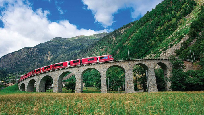 View of a red train traveling past green mountains along the curved train track, Switzerland